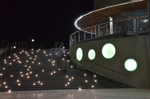 דופן גרם המדרגות המתעקל מואר בגופי תאורה קטנטנים, מפוזרים רנדומלית, יוצרים מראה של כוכבים. קירות המבנה הצמוד עם גופי תאורה עגולים בגדלים שונים, ובגוון תכלת.