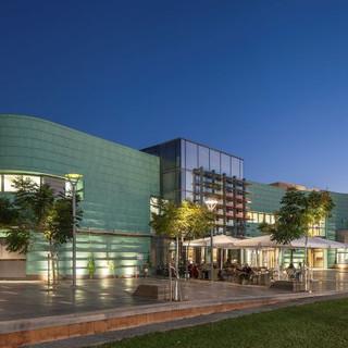 מבנה האולם מרחוק, שני חלקיו המנוגדים - הקדמי המעוגל והאחורי המחודד, מלפנים רחבת כניסה מוארת עצים, ושמיים של שעת שקיעה. צילום: עמית הס