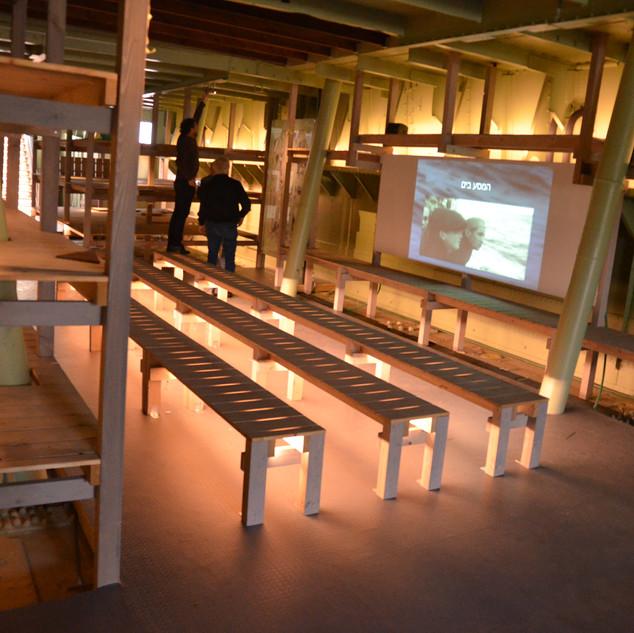 """ספסלי-עץ ב""""בטן האוניה"""" של מוזיאון ההעפלה, מוארים רק בחלקם התחתון, יוצרים אווירה המתאימה לתקופה ההיסטורית"""