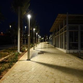 שביל צדדי - גופי תאורה ניצבים במרחקים שווים, מציירים צלליות על המדרכה