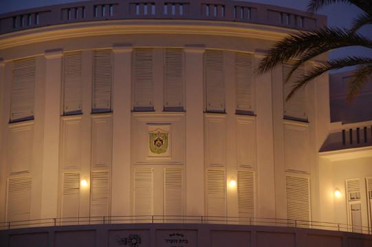 תקריב על המרפסת העליונה של בית הערייה הישן, גופי תאורה תקופתיים על הקיר, וגופי תאורה נסתרים המאירים את הקיר עצמו באור רך