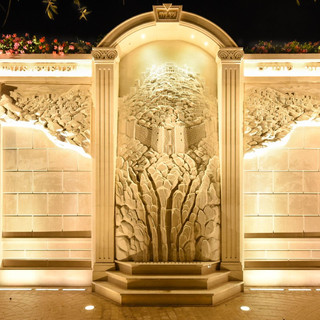 קיר התורמים - יצירת אומנות באבן, המוארת בגופי תאורה נסתרים, ומקבלת הדגש מגופי תאורה שקועי רצפה.