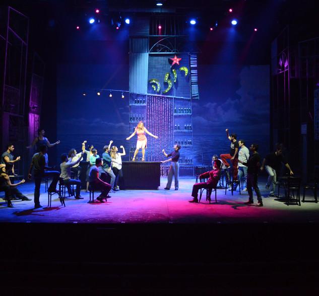 תמונה כללית של הבמה - אור של אווירה, אור ממוקד על השחקנית במרכז.