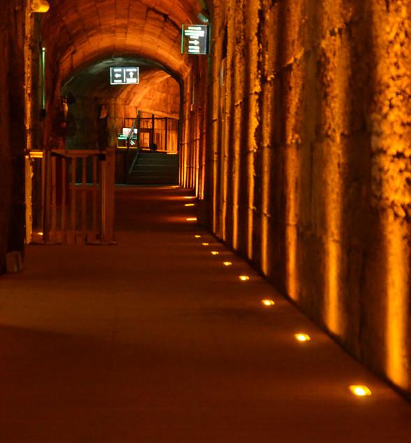 דרך הכניסה אל מחילות הכותל, גופי תאורה שקועי-רצפה, במרחקים שווים היוצרים אלומות אור על קיר האבנים הירושלמיות.