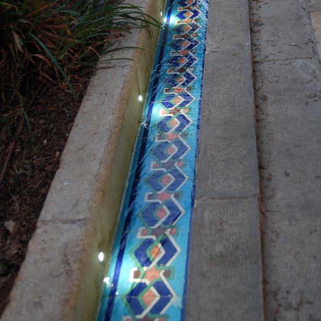 תעלת המים המקיפה את הבריכה - מבט מגבוה. גופי תאורה שקועים בדופן הקיר.