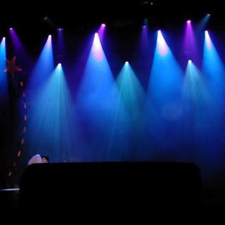 תמונת-אור כחול. אלומות סימטריות המלטפות את הבמה
