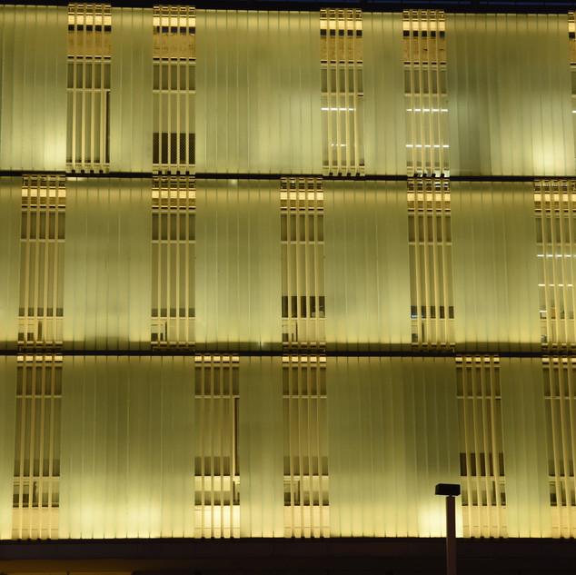 קווי המתאר האופקיים של שלוש קומות הבניין, תריסי הבטון הניצבים, ומתוכם האור זורח