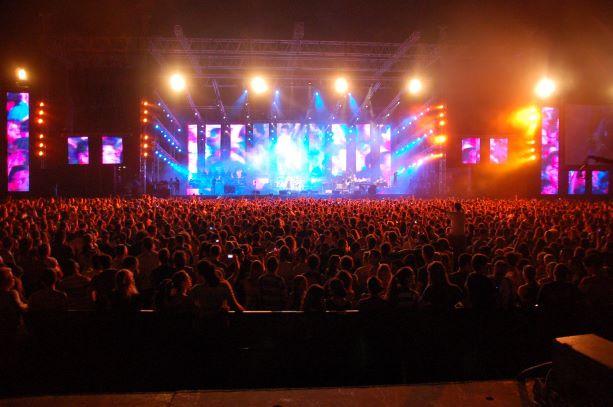 הבמה מלאה אור, וגם הקהל מואר. קונצרט רוק בפארק.