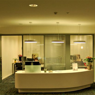 עמדת מזכירות, שלושה גופי תאורה עגולים מעל, וגופי תאורה סימטריים משני צידי העמדה
