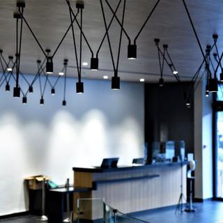 דלפק הקבלה, מואר באור ממוקד, וזווית נוספת לגופי התאורה הייחודיים של התקרה.