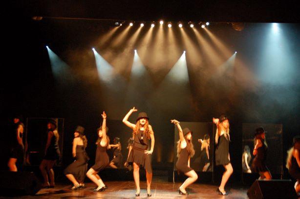 משחק של צבעים חמים וקרים באלומות האור יוצר עומק מעניין על הבמה.