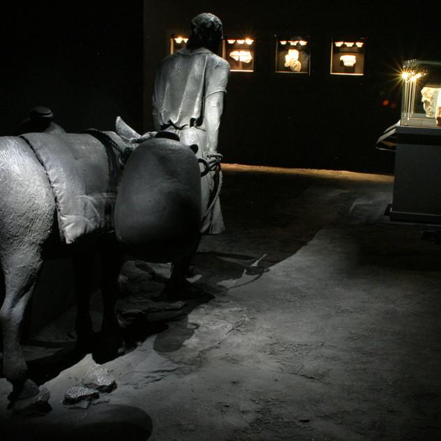 תצוגה של איכר עם חמורו. פסל ברונזה מואר באור אפרפאר. בעומק ויטרינות עם מוצגים באור חם.