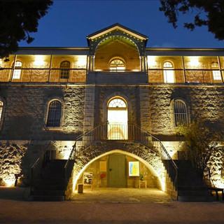 חזית בית הנסן בשעת ערב, פנסים מאירים את הבנין מלמטה
