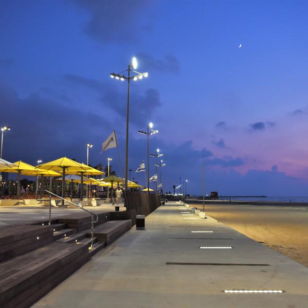 פסי לד על המדרכה, גופי התאורה הגבוהים והשמשיות משתלבים יחד לתמונת החוף המושלמת