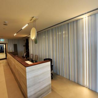 מבט מן הצד על עמדת הקבלה של המשרד. תאורה מזמינה ורכה. גוף תאורה ייחודי מעל לדלפק