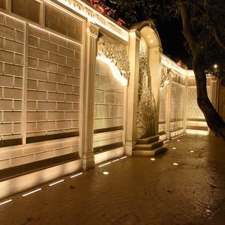 צידו של קיר התורמים. סימטריה של גופי תאורה שקועי רצפה המכוונים אל הקיר עצמו, מלמטה ומלמעלה