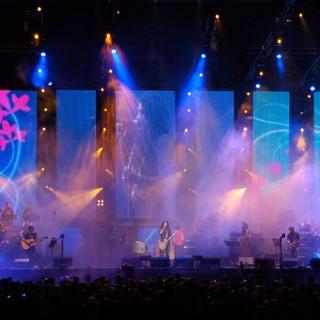 התאורה צובעת את הבמה בגוונים של טורקיז וסגול. התאורה נראית בתנועה.