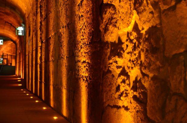 מחילות הכותל בירושלים, אלומות אור סימטריות על קיר אבנים עתיק.