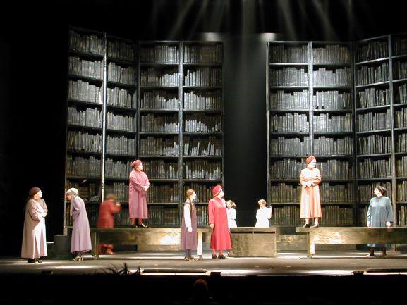 קומפוזיציה של השחקניות בתוך התפאורה. התאורה מעצימה את הספרייה הענקית הנראית בעומק.