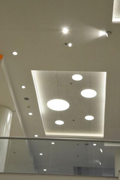 תקרה של מסדרון - משחק גיאומטרי של גופי תאורה עגולים חלקם בתוך מלבן שקוע חלקם במרחקים שווים מהקיר