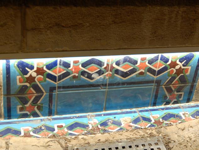 מבט מקרוב על אלמנט-קרמיקה מהתקופה העותומאנית. גוף התאורה חבוי, ומדגיש את היופי והצבעים של סף הבריכה.