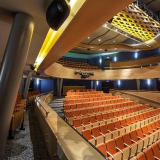 מבט מהצד על כיסאות האולם, גופי תאורה סימטריים על הקירות.  צילום: עמית גירון