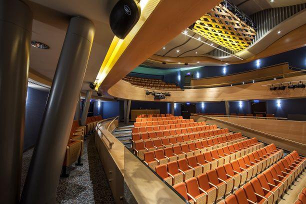 מבט מהצד על כיסאות האולם, גופי תאורה סימטריים על הקירות