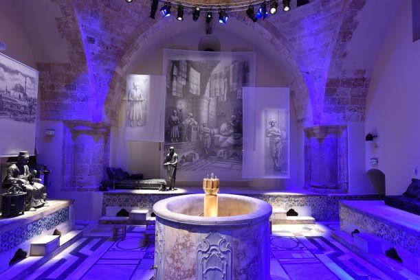 """אולם-הסבה גדול ב""""חמאם- אל באשה"""", הקירות בתאורה סגלגלה, המרכז מואר באור לבן."""