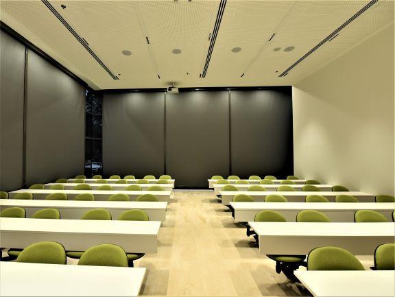 חדר הכיתה מוחשך עם וילונות. האור רך מהצדדים, מבלי שנראה מקור האור.