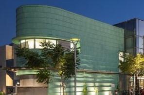 חלקו הקדמי של המבנה - תקריב. הבניין מתעגל בצורה אליפטית, אור מתחתית הבניין כלפי מעלה, ואור צהבהב מתוך החלונות