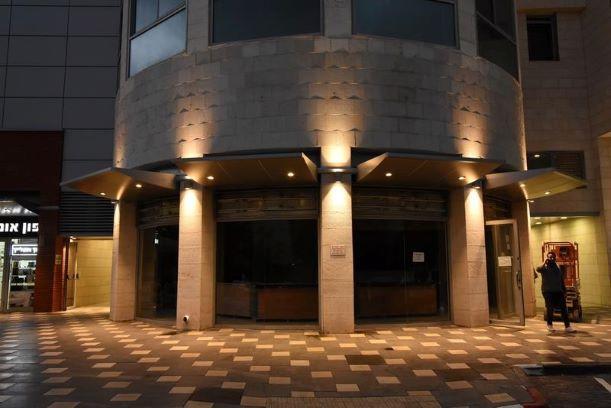 הכניסה המעוגלת, מוארת בגופי תאורה כלפי מעלה וכלפי מטה, היוצרים פסי אור במתאם לעמודי המבנה