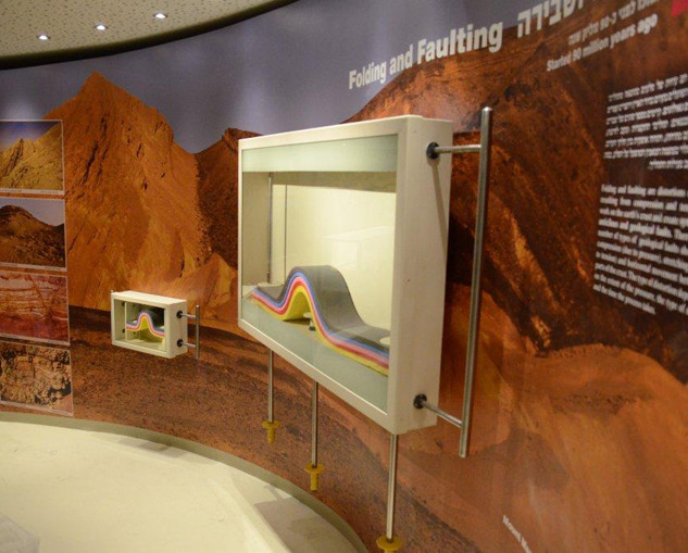 אולם-מדברי במרכז המבקרים. הדגמה של דיונות המדבר. תאורה בהירה, בגווני צהוב.