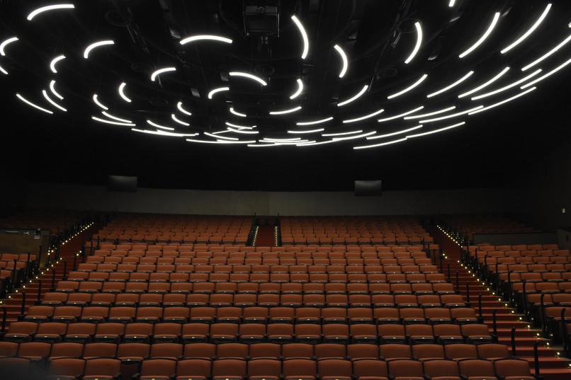 גופי תאורה מאורכים, מסודרים בכמה טבעות של עיגולים, יוצרים מראה של שנדליר ייחודי מעל כסאות המושבים באולם תיאטרון ויקס, רחובות