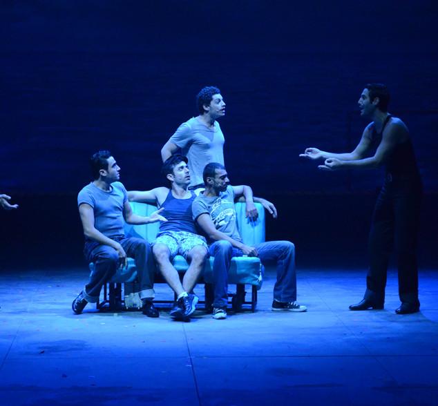 אור כחלחל על חבורת שחקנים במרכז הבמה.