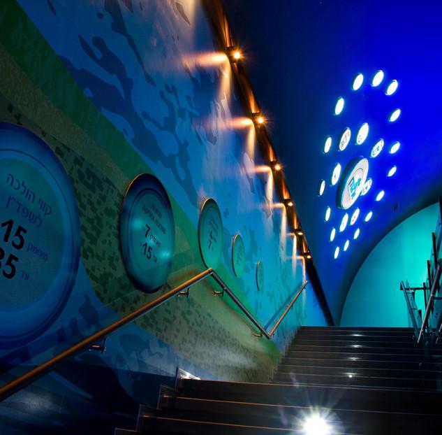 מדרגות הכניסה לתצוגה. הקירות בגוונים של כחול, טורקיז וירקרק, איקסים של אור הנוצרים בעזרת גופי תאורה צמודי-קיר