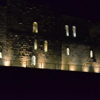 הבנין העתיק מואר בלילה, גם מתוך החלונות, גם מכיוון האדמה, במרחקים שווים. הקיר דרמטי ועוצמתי