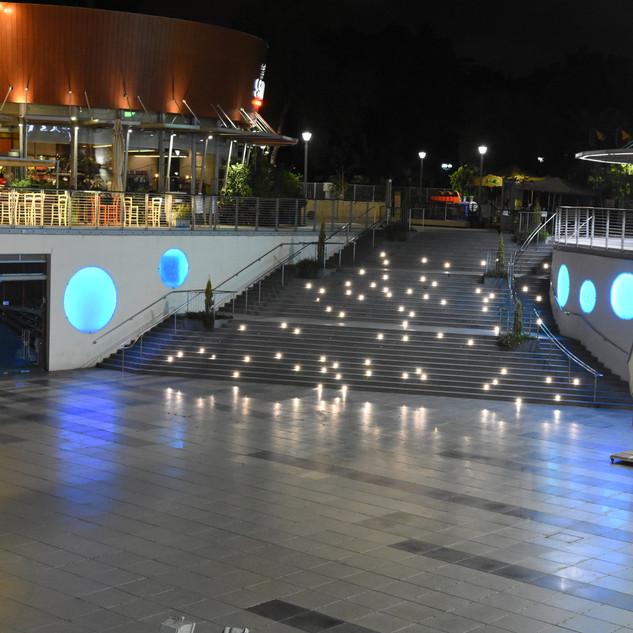 מבט על כל מתחם המבנים של הפארק. הבנין המעוגל, המדרגות עם נצנוצי הכוכבים ורחבת ההליכה עליה משתקפת התאורה הקסומה