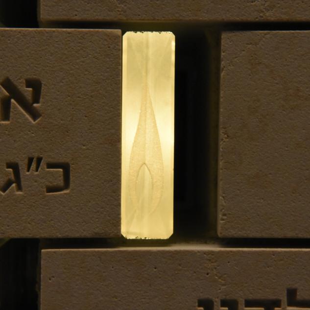 תקריב של גוף התאורה הייחודי הנראה כמו שלהבת נר-נשמה, שהומצא ועוצב על ידי עמיר ברנר