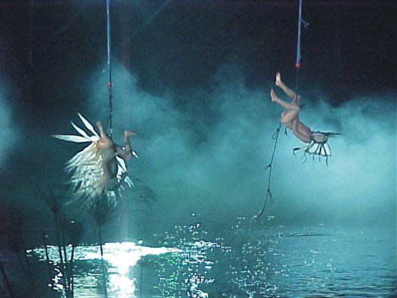 רקדנים-שחקנים תלויים מעל המים, תמונה של בריאת העולם. אור כחלכל