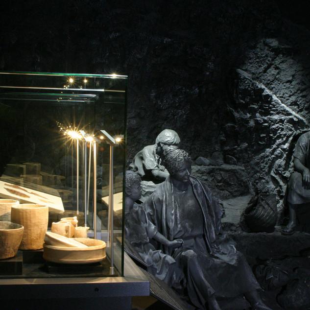 ויטרינה תצוגה עם כדי עתיקים מוארת באור חם, ולידם פסלי ברונזה בתצוגה מוארים באור כחלכל