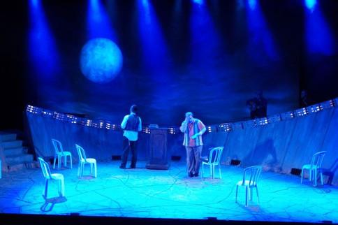 """תאורת-במה להצגה """"זהב טורקי"""", תיאטרון הקאמרי, אלומות אור כחול, וירח גדול מאחור."""