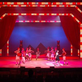 בעומק הבמה צלליות של פירמידות. בקדמת הבמה אור ממוקדר על הכוכבת המספרת את הסיפור