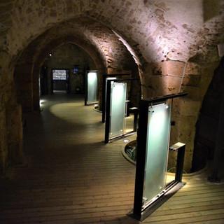 מסדרון במצודה. עמודי-המידע למבקרים מוארים באור ממוקד. עמודי המבנה מודגשים בתאורה המאירה מלמטה למעלה