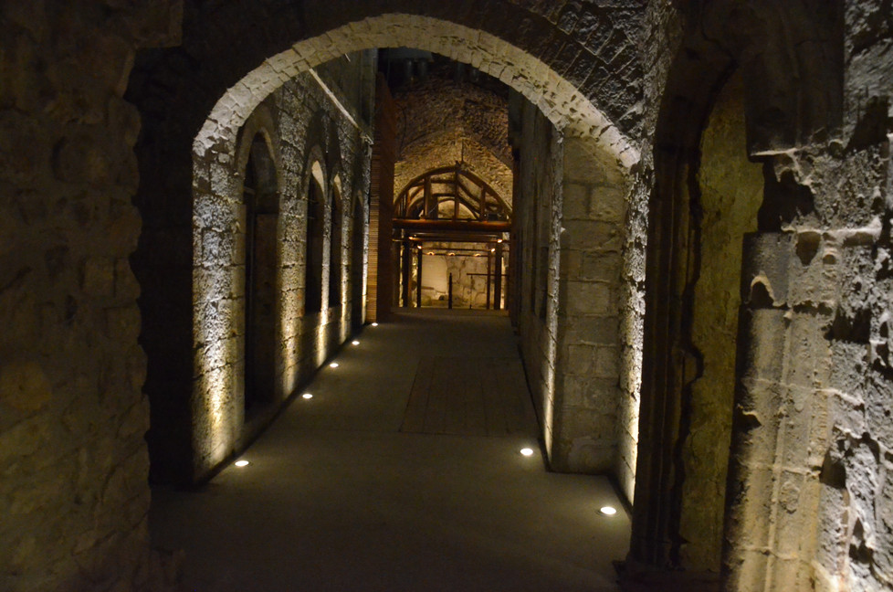 """מסדרון-אבן עתיק, גופי התאורה שקועי רצפה, ומאירים את הלבנים הדרך מובילה אל אולם """"אחורי-כותלינו"""" מחילות הכותל, ירושלים"""