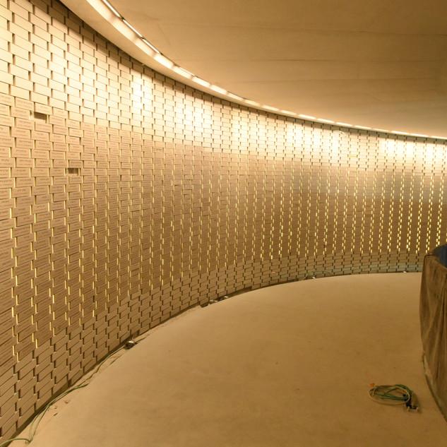 קיר השמות באתר ההנצחה, תאורה נסתרת מלמעלההמאירה את הקיר המתעקל