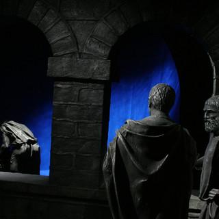 פסלי ברונזה של שלוש דמויות בתצוגת המוזיאון. ברקע מסך מואר בגוון כחול עמוק