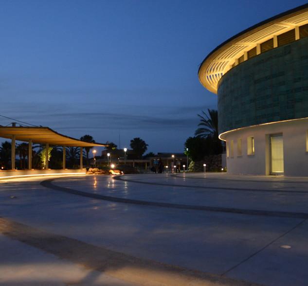 מבט מהצד על המבנה והרחבה שלפניו. התאורה מדגישה את הקו המעוגל של הבניין. לצד הבנין פרגולת מפרש. פס התאורה מתכתב עם קו המתאר העגול של הבנין
