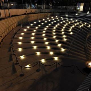 גופי התאורה במדרגות הכניסה בוהקים באור, מדגישים את המדרגות, ומשרים אווירה ייחודית