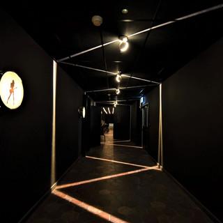 מסדרון עם פסי אור ייחודיים המייצרים זיג-זג של אור על הקירות ועל הרצפה