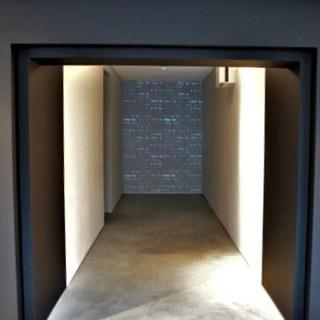 פתח הכניסה. קיר כהה, וממנו יוצא מסדרון המאור בתוכו, מוביל את המבקרים להכנס.